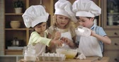 farinha : Group of lovely children pouring flour into egg mixture