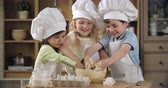 farinha : Three lovely kids trying to knead dough in cooking class