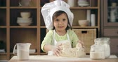farinha : Adorable little girl in apron and chef hat kneading dough