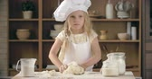 avental : Beautiful little girl kneading pastry dough in domestic kitchen