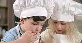 avental : Adorable children tasting sweets in cooking class