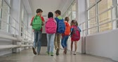 dzieci : Rear view of school kids with backpacks walking along corridor