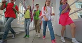 dzieci : Happy elementary students running along corridor towards the camera