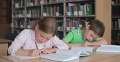 pupil : Concentrated school students sitting at desk and doing tasks Stock Footage