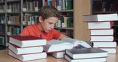 ciência : Exhausted schoolboy doing a research surrounded by stacks of books Vídeos