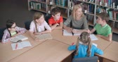 изучение : High angle view of a teacher and a group of elementary students discussing ideas