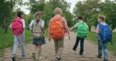 dostihy : Rear view of group of elementary students with backpacks walking together through park and starting running