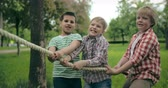 desafio : Three little boys taking part in tug of war competition