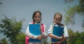 Öğrenciler : Two lovely schoolgirls with workbooks in their hands walking outdoors and talking