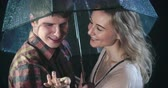романтический : Romantic young couple talking under umbrella in rain and finally kissing