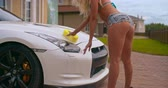 sedutor : Sexy young woman seductively washing a white sports car