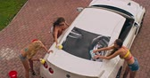 vysoký úhel : High angle view of three pretty girls washing an automobile