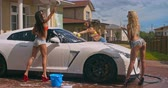 sedutor : Group of seductive hot girls having fun while washing a white sports car Stock Footage