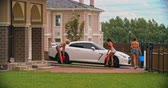 sedutor : Three hot models walking out of a house and starting to wash a sports car Stock Footage