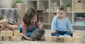 bloco : Cheerful little girl and her cute baby brother playing with a fluffy kitten in nursery room