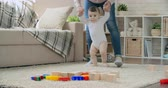 mama : Young mother teaching her adorable baby son to walk and play with toy blocks