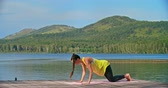 joga : Beautiful young woman having outdoor yoga practice near lake Wideo