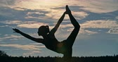 joga : Silhouette of a woman doing lord of the dance yoga pose in nature at dusk