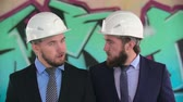 здание : Close-up of two twin architects in helmets shaking heads in slow motion Стоковые видеозаписи