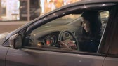 automóvel : Young woman dialing a number and talking on her smart phone sitting in car Stock Footage
