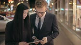caminhada : Young couple using digital tablet in street at night in slow motion