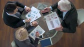 dados : High angle of three business partners discussing in meeting, a senior businessman explaining his point of view