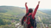 satisfação : Panning shot of female hiker raising up her arms to celebrate success at the hilltop