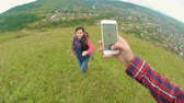 pov : Hiker photographing his girlfriend on hilltop with smart phone and showing her pictures