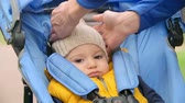 örgü : Sad baby boy sitting in buggy stroller, his mother pulling down knit hat over his ears