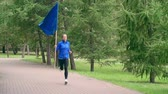 başarı : Female athlete with a blue flag running through the park in slow motion Stok Video
