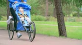 pram : Cropped woman running with her baby son sleeping in a jogging stroller