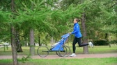 pram : Slow motion shot of a fit mother running through the park with a jogging stroller Stock Footage