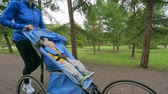 pram : Baby boy sleeping peacefully in a jogger pushed by his fit mother Stock Footage