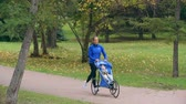 pram : Female athlete running in autumn park with her baby sleeping in jogging stroller Stock Footage