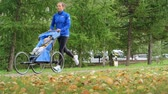 empurrando : Fixed-frame low angle shot of a fit woman training for a marathon with her baby in jogger