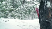 снег : Cheerful little girl hiding behind a tree trunk during snowball fight