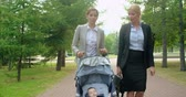 pram : Tilt up of two business women talking on the move, one of them pushing a stroller with her lovely baby son