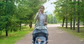 pram : Confident young businesswoman talking on cell phone while walking through a park with her baby boy napping in pram Stock Footage