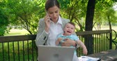 working parents : Business mom discussing on the phone and trying to soothe her crying baby son Stock Footage