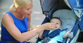 beslenme : Caring mom feeding her lovely baby boy with a spoon