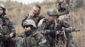 militar : Soldiers taking a rest during an assault, smoking and discussing a strategy