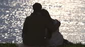 романтический : Back view of embracing couple looking at lake
