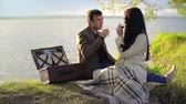 margem do rio : Beautiful couple toasting with red wine and kissing during romantic picnic on riverbank Stock Footage