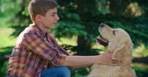 walk : Side view of teenage boy stroking his dog and a putting collar on its neck Stock Footage