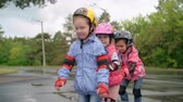 empurrando : Three little girls wearing rollerblades skating in a row in slow motion
