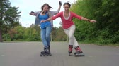 конькобежец : Two cheerful girls rollerblading together and doing a trick with crossed legs in super slow-motion