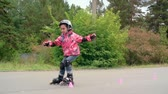 кататься на коньках : Little girl roller skating between cones in slow motion