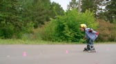 кататься на коньках : Cute little inline skater learning to skate between cones Стоковые видеозаписи