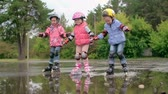 кататься на коньках : Group of kids roller skating through puddles in slow motion