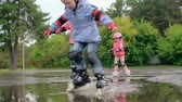 кататься на коньках : Slow motion shot of kids skating through puddles and splashing water Стоковые видеозаписи